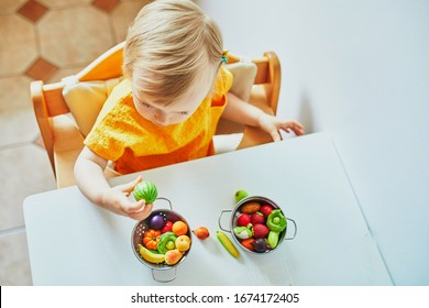 Little girl playing with toy fruits and vegetables at home, in kindergaten or preschool. Game activities to play with a child at home