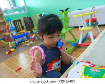 little girl playing toy phone,Little girl is lifting the toy phone up to the ear,Little girl in a room full of toys