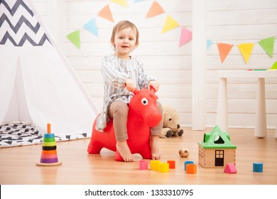 Little girl playing with toy red horse at home