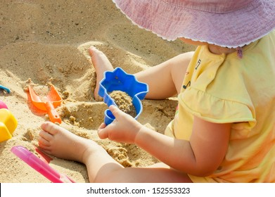Little girl playing with toys in the sand