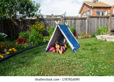 Little girl playing with toys in a tent on the grass in the garden