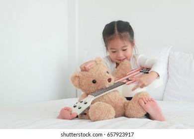 Little girl playing ukulele.