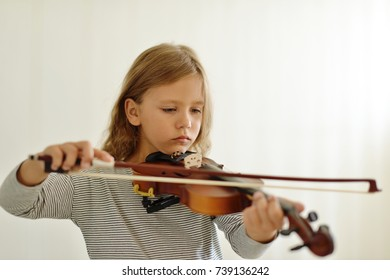 little girl playing the violin at home