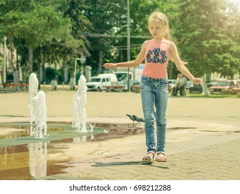 Little girl playing with water in city fountain. The concept of happy children's day in the sun.