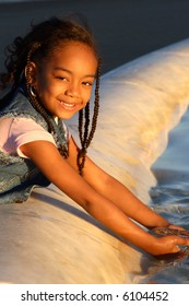 A little girl playing in the water highlighted by the golden evening sun