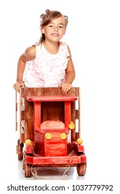 Little girl is playing with a wooden car. The concept of a happy childhood, playing in a kindergarten and family. Isolated on white background.