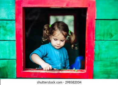 Little girl playing in wooden house  in nature