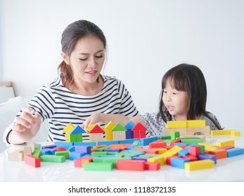 Little girl playing wooden toy with her mother at home on weekend.