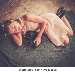 Little girl playing with yorkshire terrier puppies.