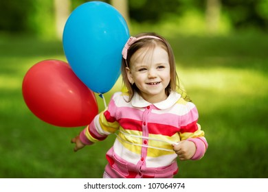 little girl plays with balloons
