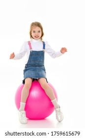 Little girl plays with a big ball for fitness
