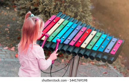 A little girl plays a colorful xylophone in the park.