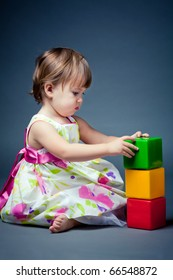 little girl plays with cubes