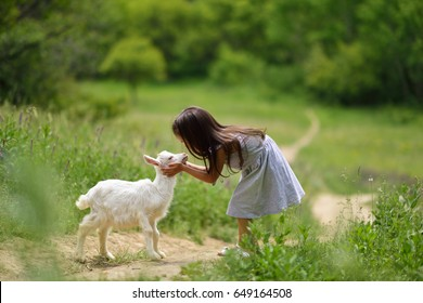 Little girl plays and huhs goatling in country, summer nature outdoor. Cute kid with baby animal, countryside outdoor portrait, forest, trod, glade background. Friendship of child and yeanling