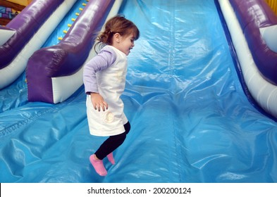 Little girl plays and jumps on Inflatable giant slide.