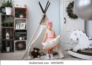 The little girl plays in a nursery with a New Year's interior.