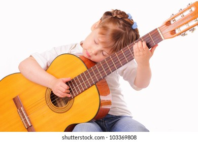 Little girl plays an old guitar