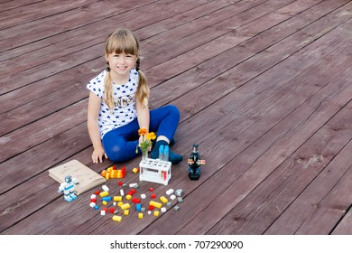 Little girl plays on the flore. Microscope and flowers are near her. Little robots. E-learning. Stem education. Back to school.
