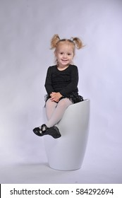 Little girl plays on a white chair in the studio on a photo shoot. A child dressed in the dark. Funny pictures.