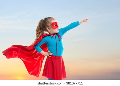 Little girl plays superhero on the background of sunset sky. Power concept.