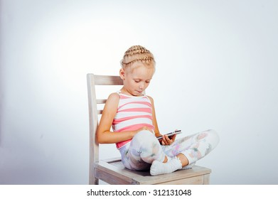 little girl plays with a tablet
