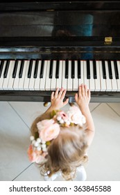 little girl plays a tune on the piano keys. Piano school for little girl