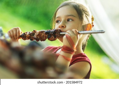 Little girl with pleasure eats shish kebab