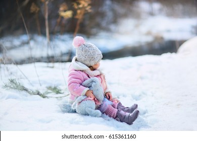 Little girl with plush bunny in winter park