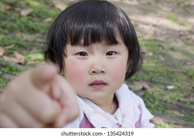 a little girl point you in nature.