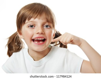 little girl pointing her missing teeth
