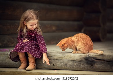 Little girl is pointing on a piece of sausage to a big red cat  in the country in Russia. Image with selective focus and toning