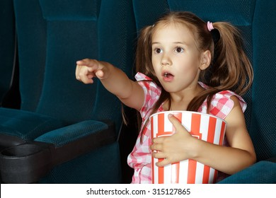 Little girl pointing to screen during film