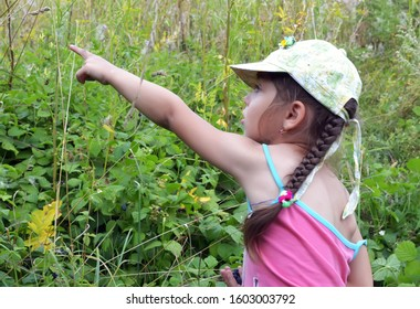 little girl points a finger the right direction in the bushes