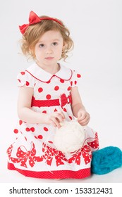 Little girl in a polka dot dress and rim with a bow unravels a ball of yarn