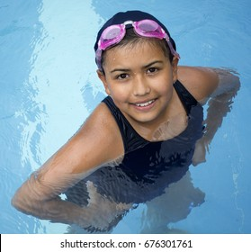 Little girl in pool with blue swimming cap and goggles pink.