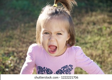 Little girl portrait outdoor screaming grasping defending her opinion