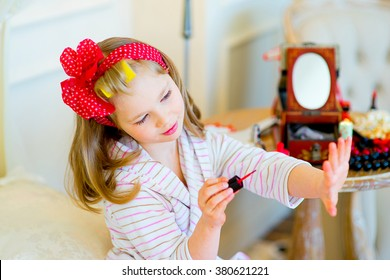 the little girl poses in pin up style in a striped terry dressing gown, in hair curlers and with a red bandage in peas paints nails