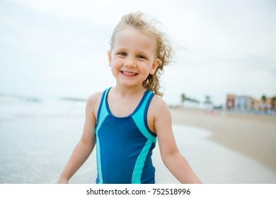 Little girl posing against the coastline, smiling
