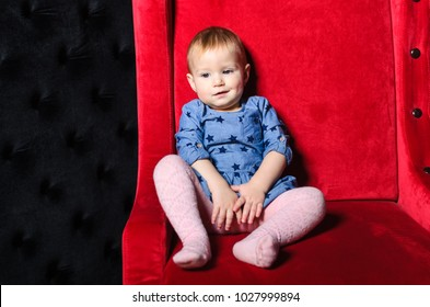 little girl posing in Studio. the girl one or two years . sitting on a red chair