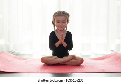 The little girl practices yoga in a black sports swimsuit. Girl in lotus position with closed eyes