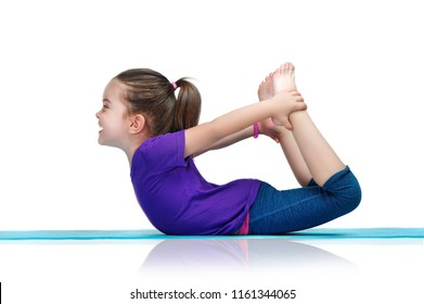 Little girl practicing bow yoga pose laying on belly