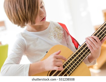 Little girl practicing playing small bass guitar