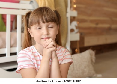 Little girl praying at home