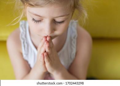 Little girl praying at home