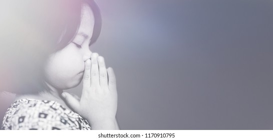 Little girl praying in the morning at home.Little asian girl hand praying for thank GOD,Hands folded in prayer concept for faith,spirituality and religion.black and white tone.