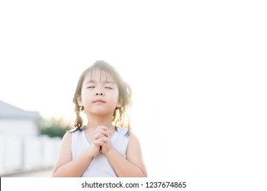 Little girl praying in the morning at home.Little asian girl hand pray for thank GOD on white background,Hands folded in prayer concept for faith,spirituality and religion.