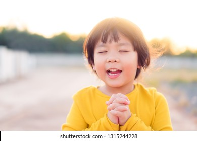Little girl praying in the morning for a new day.Little asian girl hand praying for thank GOD,Hands folded in prayer concept for faith,spirituality and religion.