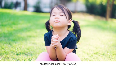 Little girl praying in the morning at park.Little asian girl hand praying and looking up to sky,Hands folded in prayer concept for faith,spirituality,worship and religion.