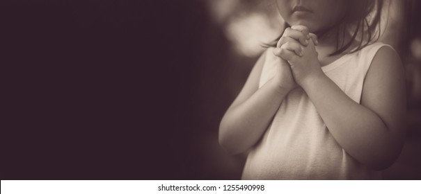 Little girl praying in the morning.Hands folded in prayer for faith,spirituality and religion.Concept for violence,homeless people,kidnapping,violence,terrified,Human Rights.Sepia vintage tone.