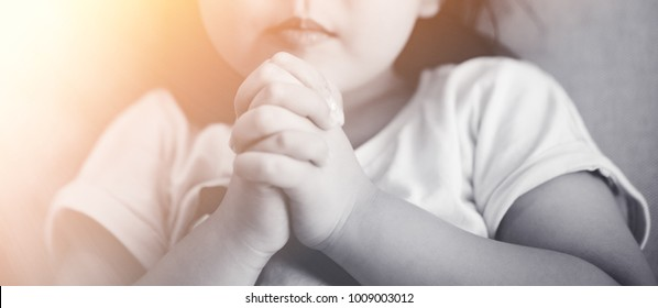 Little girl praying in the morning.Little asian girl hand praying to GOD,Hands folded in prayer concept for faith, worship, spirituality and religion.Black and white tone.